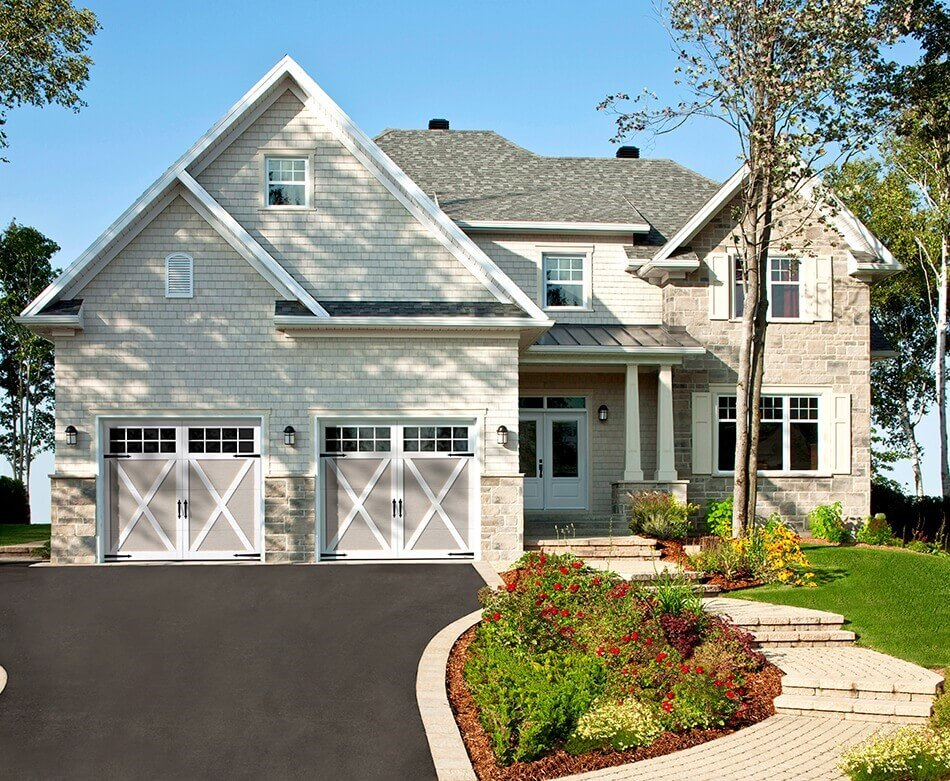 Traditional house with garage doors: Eastman E-21, 9' x 7', Claystone doors and Ice White overlays, 8 lite Panoramic windows