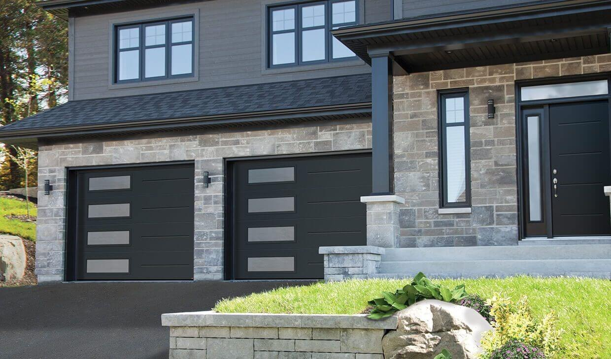 Modern home, light gray stone and iron gray wood, with 2 garage doors in Vog design, 9'x7', Black, Left‑side Harmony window
