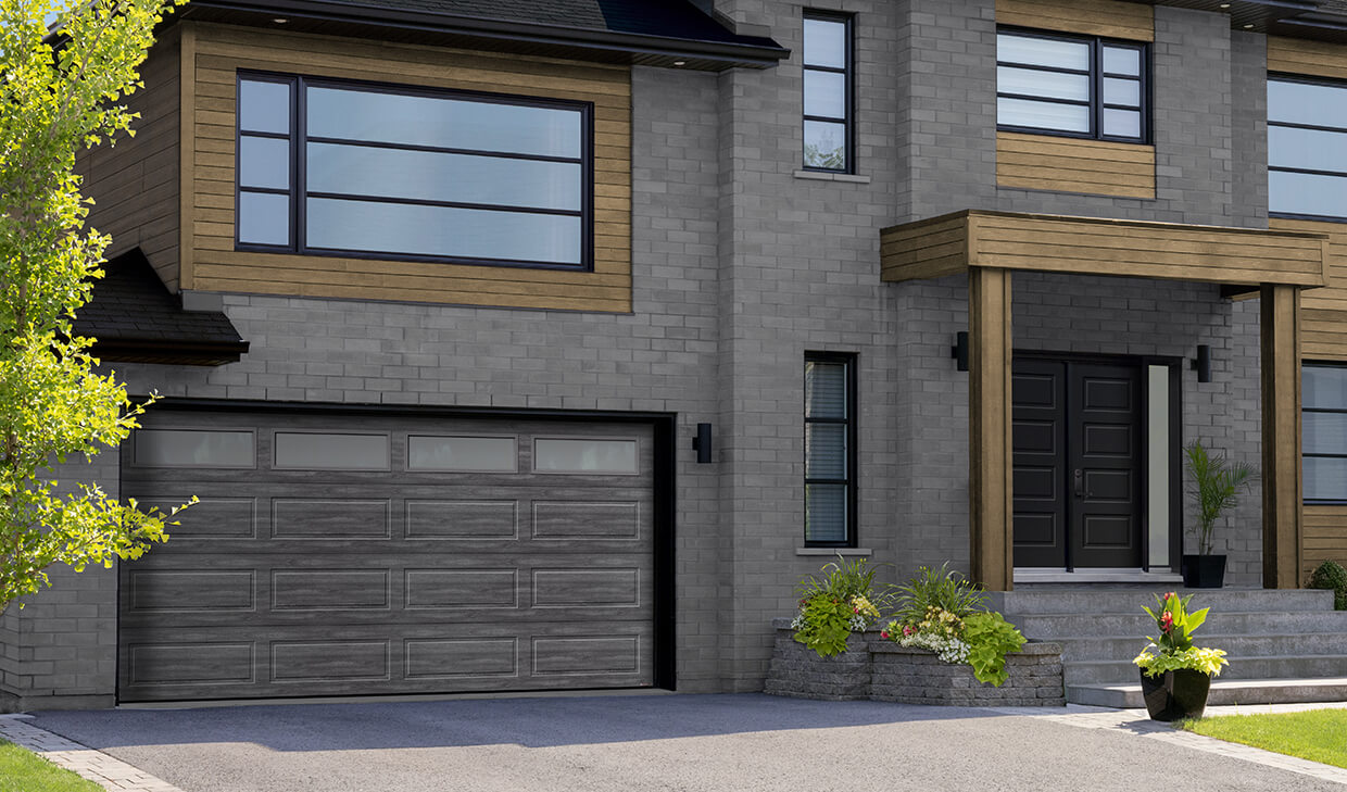 Modern house with a two car garage door in the Shaker-Modern XL design and Iron Ore Walnut color