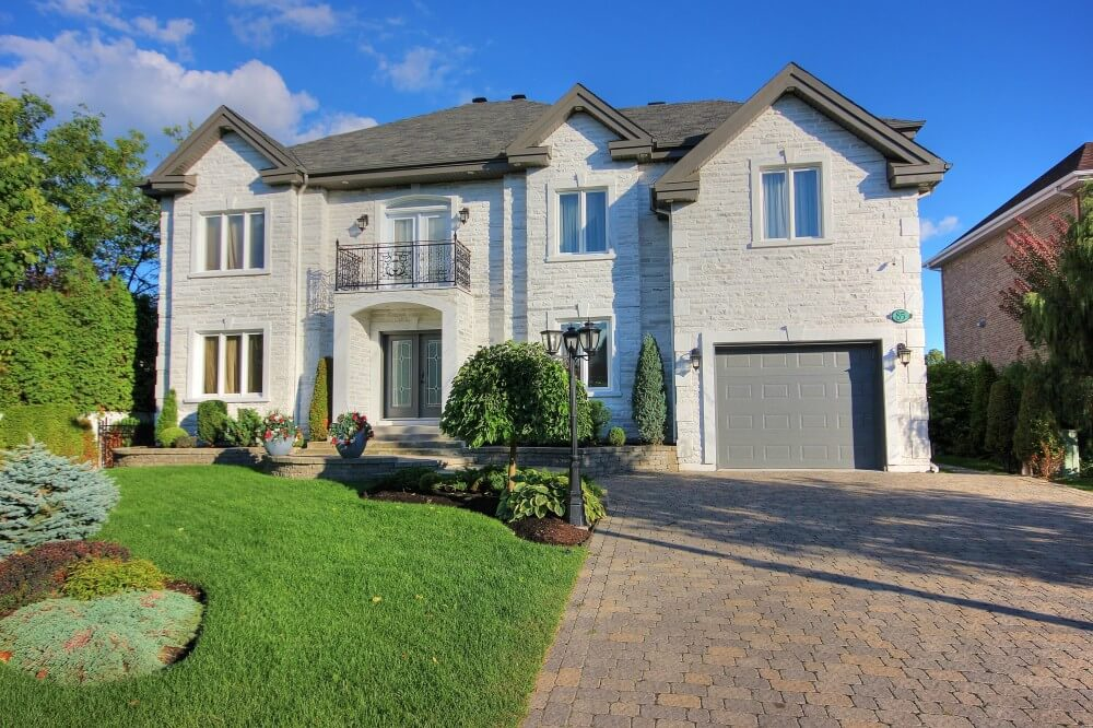 Traditional 2-storey grey brick house with master bedroom above the garage