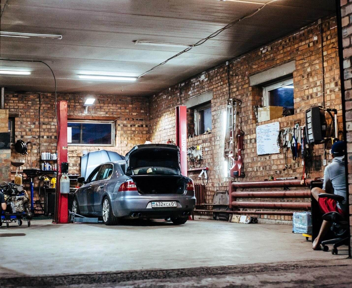 A garage interior with a man working on his car.