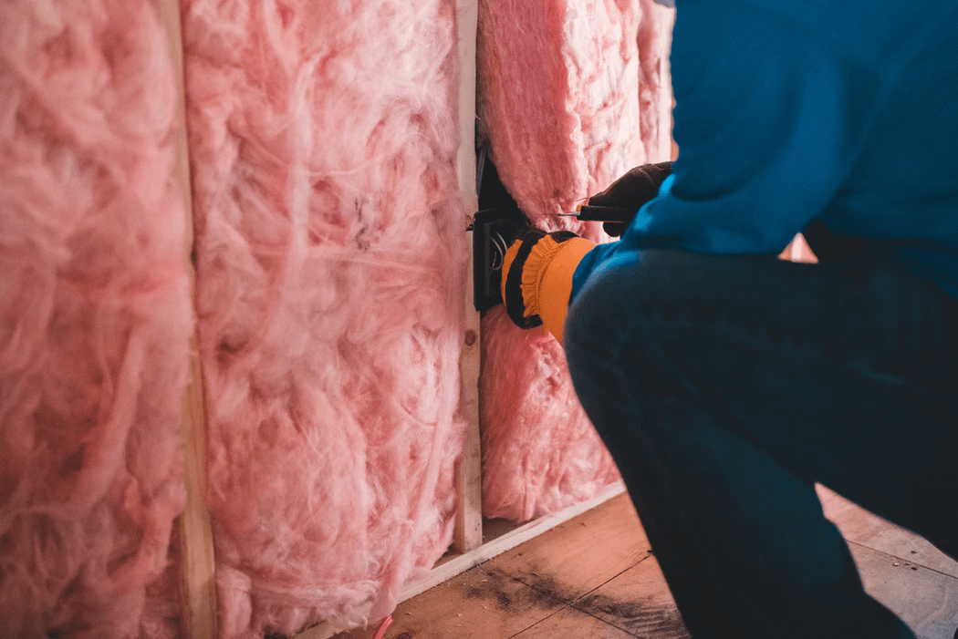 Someone isolating a wall with mineral wool.