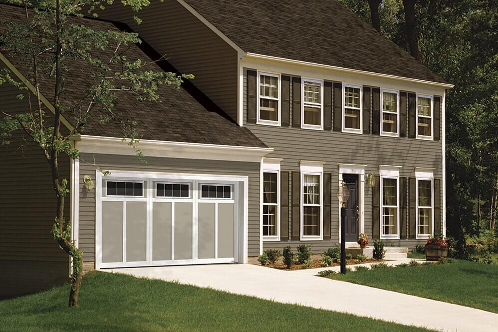 Cette magnifique maison traditionnelle est rehaussée d'une porte de garage Garaga, Eastman E-12, 14' x 7', Couleurs: portes Argile et moulures Blanc Glacier, avec fenêtres