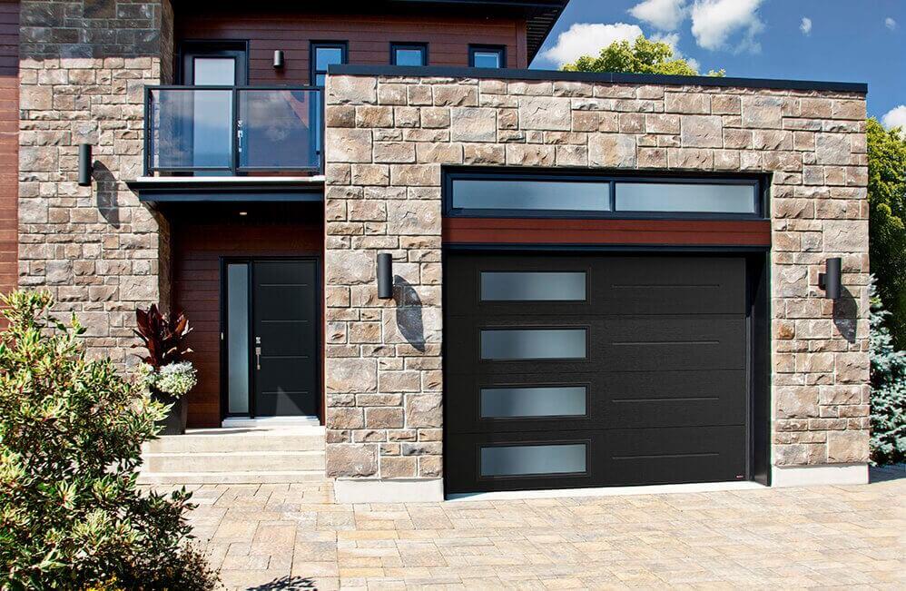 La pierre aux tons chauds et le bois caramel de cette maison de style Contemporain sont rehaussés par une porte de garage Garaga, au desing exclusif Vog, de couleur Noir, avec une rangée verticale de fenêtres pour une belle touche moderne et beaucoup de lumière naturelle