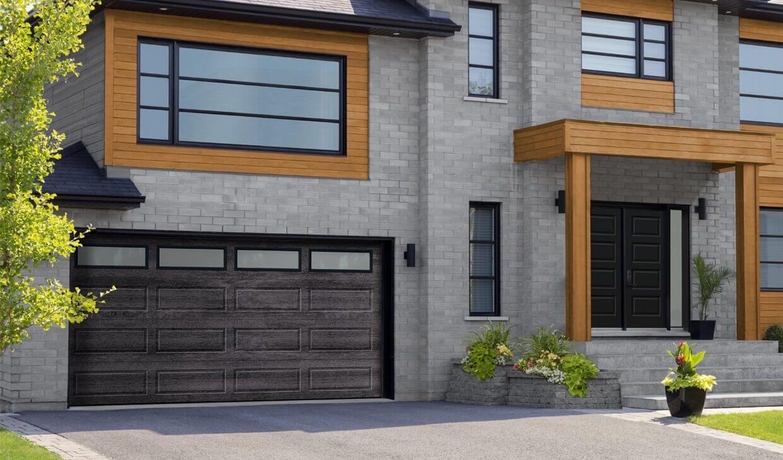 Maison de style Contemporain en brique grise, rehaussé de bois blond, avec une porte d'entrée noir et une porte de garage de couleur Noyer minerai de fer