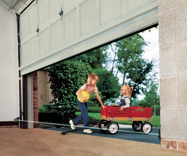 Two little girls playing close to a garage door while closing. The photo-cell safety beams are activated for more safety.